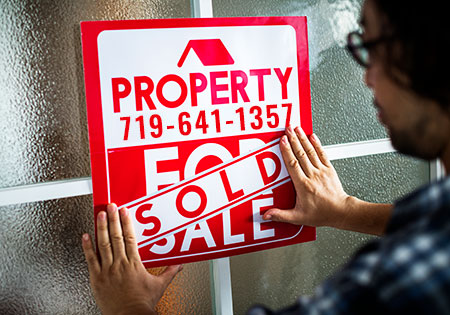 Man putting sold sign on for sale sign